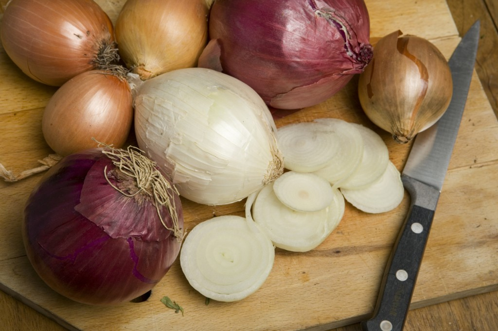 Various different types of onion on a chopping board